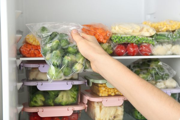 Woman Putting Plastic Bag With Brussels Sprouts In Freezer