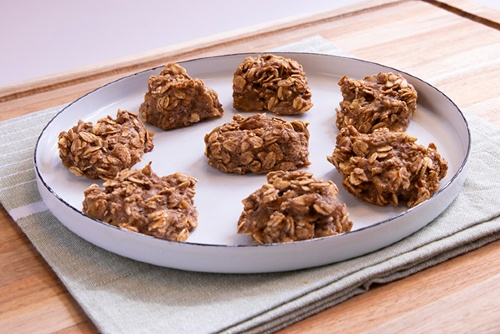 Plate of oatmeal drop cookies sits atop a napkin and wooden board