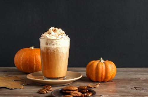 Pumpkin spice latte topped with whipped cream and surrounded by mini pumpkins