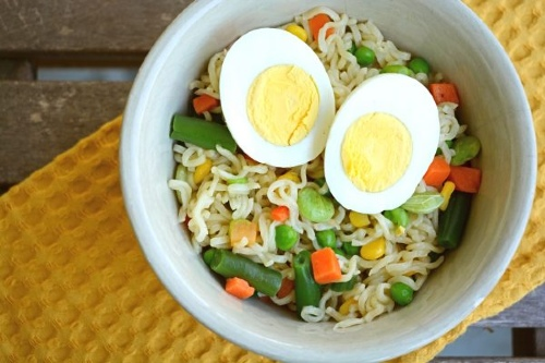 Bowl of ramen noodles with colorful veggies and a hardboiled egg