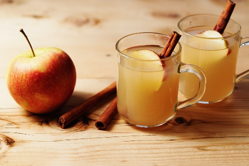 Apple cider in clear mugs with apple slides and a cinnamon stick