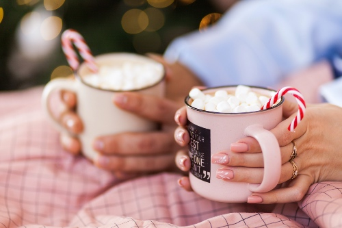 Couple sitting under a blanket both holding mugs of hot chocolate with candy canes