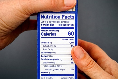 Hands hold the side of a blue food box with the nutrition facts label