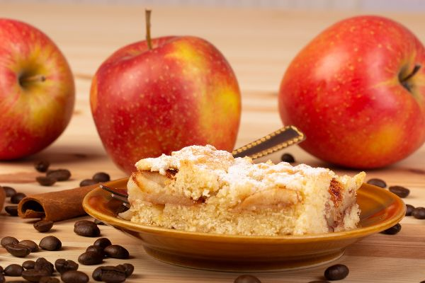 coffee cake on a plate with 3 apples and coffee beans