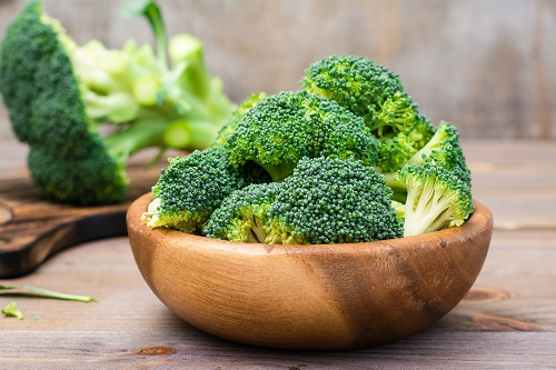 Wooden bowl of raw and cut broccoli florets