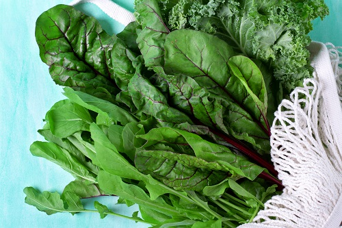 Chard, kale and arugula in a white mesh bag on a blue table.