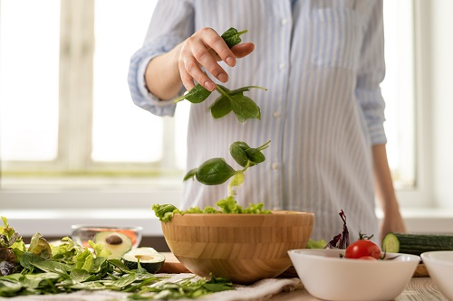 close up pregnant woman in blue shirt assembling a salad with spinach leaves