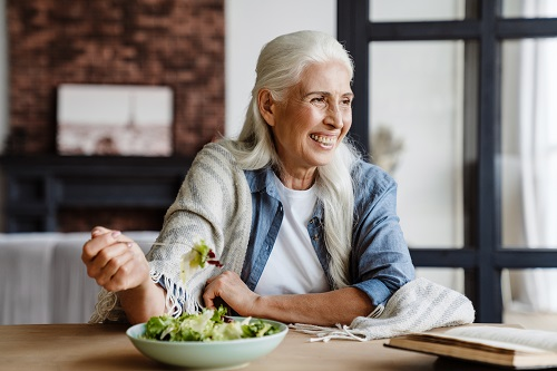 Smiling senior woman reading a book while sitting in the kitchen, eating salad