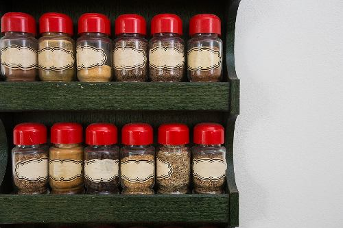 jars of herbs and spices on a wooden, two-tiered rack