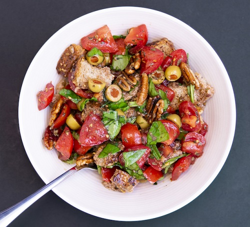 colorful salad with bread, tomatoes, olives, greens, and pecans in a white bowl with a silver spoon