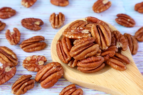 Wooden Spoon Full of Pecan Nuts with Many Scattered on Pale Blue Wooden Table