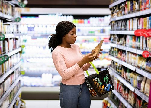 young female shopping in a grocery store aisle reading a food label